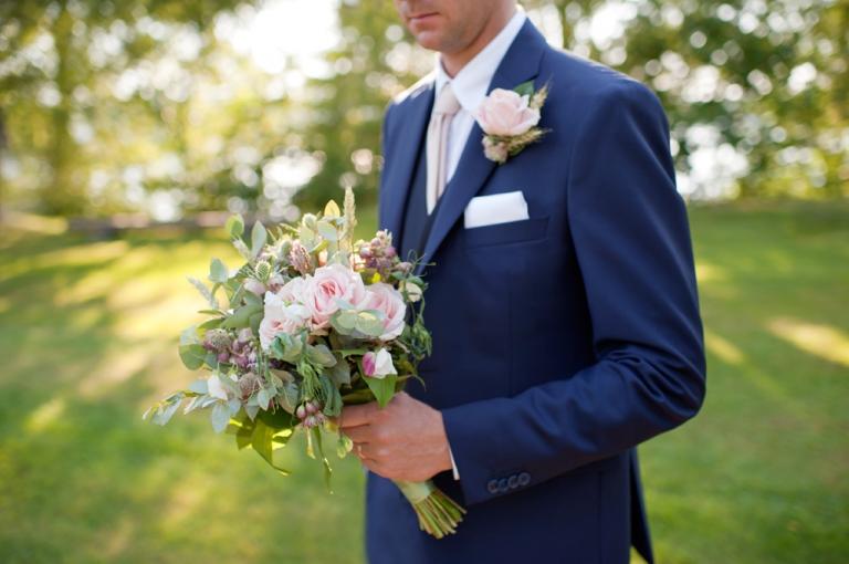 Brudgum håller i brudbukett i Leksand i vackert ljus